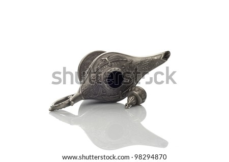 Oil lamp east design with egypt or arabic texture lying on the white background and a cap lying near it - stock photo