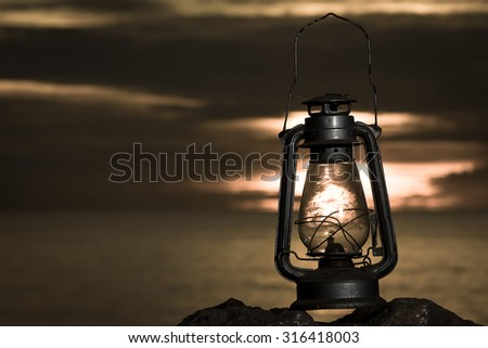 oil lamp on the beach at sunrise .