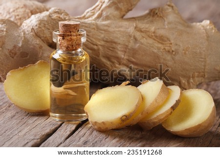 oil of ginger in a small glass bottle macro and root on the table, horizontal - stock photo