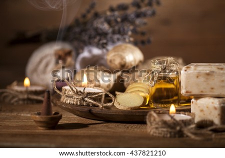 Oil of ginger in a small glass bottle macro and root on wooden table. Health spa background. - stock photo