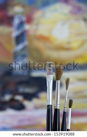 Oil paint brushes and a painting - stock photo