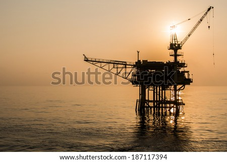 oil platform silhouette when sun set - stock photo