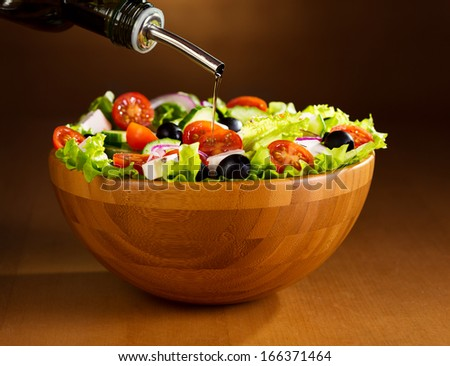 oil pouring into bowl of greek salad - stock photo