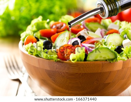 oil pouring into bowl of salad - stock photo