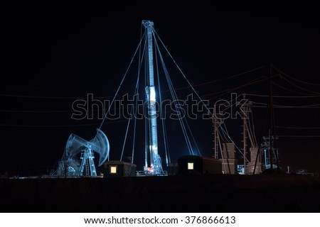 Oil pump jack and drilling rig at the night sky background. Oil fields in Western Siberia.
