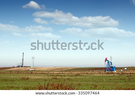 oil pump jack and land drilling rig on field - stock photo