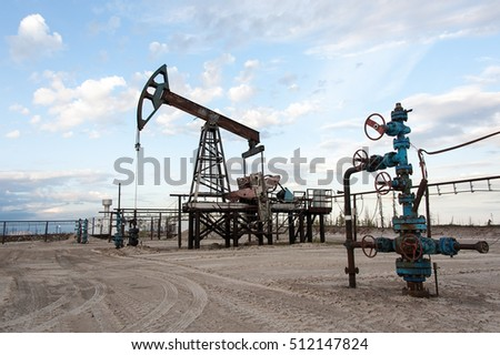 Oil pump jack and wellhead with valve armature during sunset on the oilfield. Extraction of oil. Oil and gas concept.