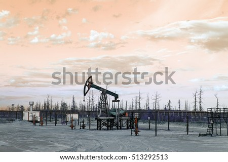 Oil pump jack and wellhead with valve armature during sunset on the oilfield. Extraction of oil. Oil and gas concept. Toned.