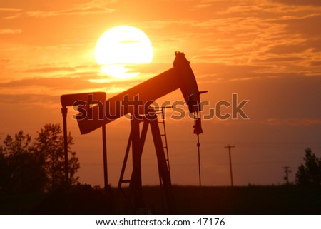 oil pump jack in silhouette - stock photo