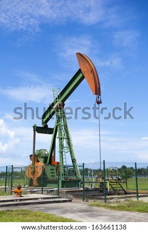 Oil pump jack in work. Oil industry in Seria, Brunei Darussalam on a sunny day with cloudy blue skies. - stock photo