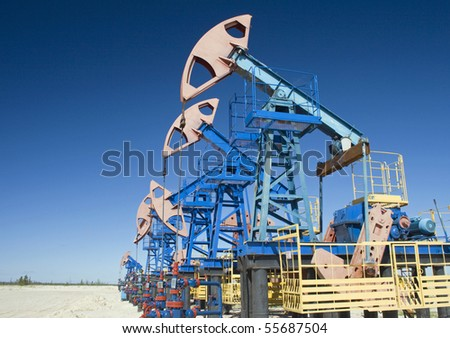 Oil pump jack on a sand - stock photo