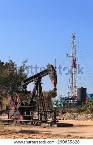 Oil Pump Jack (Sucker Rod Beam) and Drilling Rig on Sunny Day - stock photo