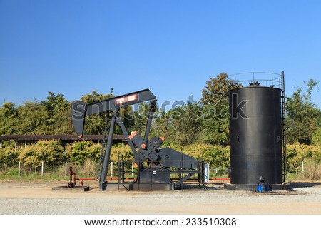 Oil Pump Jack (Sucker Rod Beam) and Reserve Tank on Sunny Day - stock photo