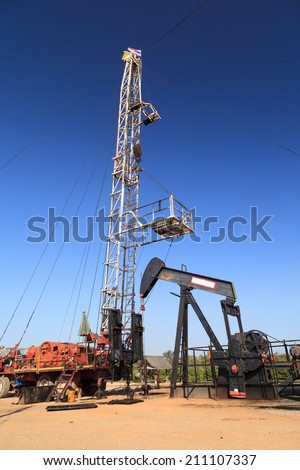 Oil Pump Jack (Sucker Rod Beam) and Workover Rig Working on Oil Well on Sunny Day