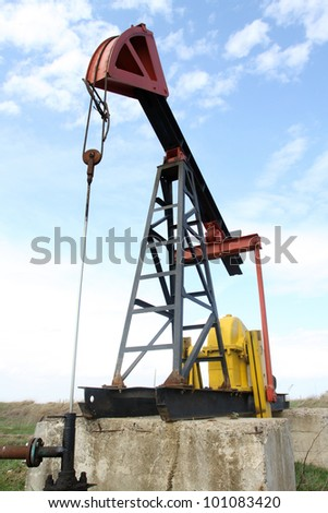 Oil pump jack working in the field - stock photo