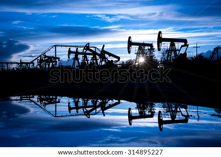 Oil pump jacks group on a sunset sky background. Toned blue.