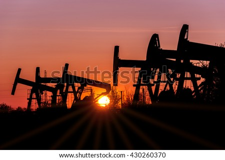 Oil pump jacks on a oilfield at sunset sky background. Concept oil and gas industry.