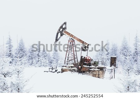 Oil pump. Oil and gas industry equipment. Oil field pump jack and oil refinery in the winter with snow, mountains and forest in background. In a snowy haze. - stock photo