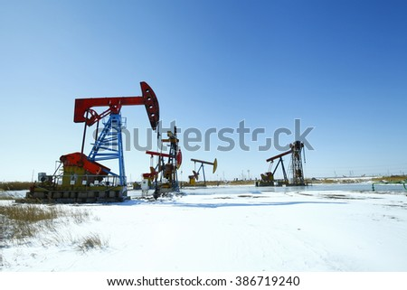 Oil pump, oil industry equipment in the snow - stock photo