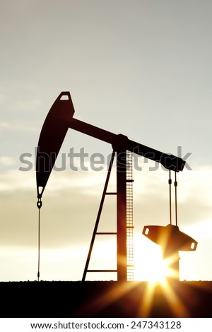 Oil pump oil rig energy industrial machine for petroleum in the sunset background - stock photo