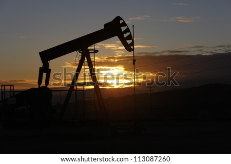 Oil pump on an oil well on the Midway-Sunset oil field near Taft, California at dawn.