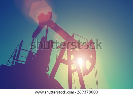 Oil pump on background of blue sky - instagram style - stock photo