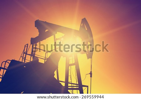 Oil pump on background of red (orange) sky - instagram style - stock photo