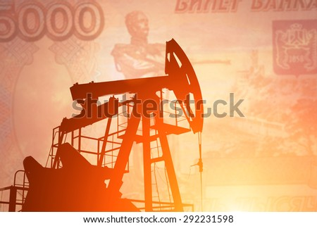 Oil pump on background of russian rouble - stock photo