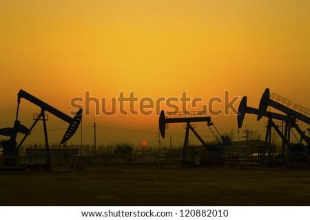 Oil Pump on orange sunset - stock photo
