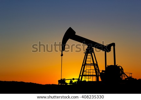Oil pump silhouette over sunset sky