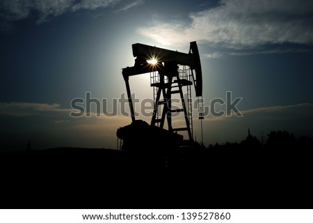 Oil pump with sun beams going trough the machine. - stock photo