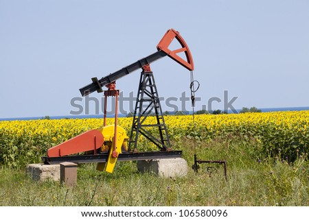 oil pump with sunflowers field on the background