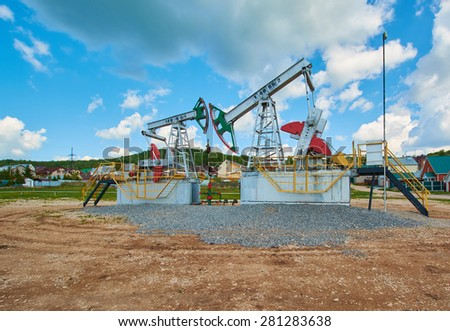 Oil pumping station machine rocking spring against the sky - stock photo
