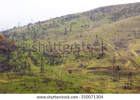 Oil pumps at large oilfield over mountain range. An oil well servicing rig sets up in mountainous country. A cluster of pumping units (oil wells) located in the foothills of the Shabran, Azerbaijan. - stock photo