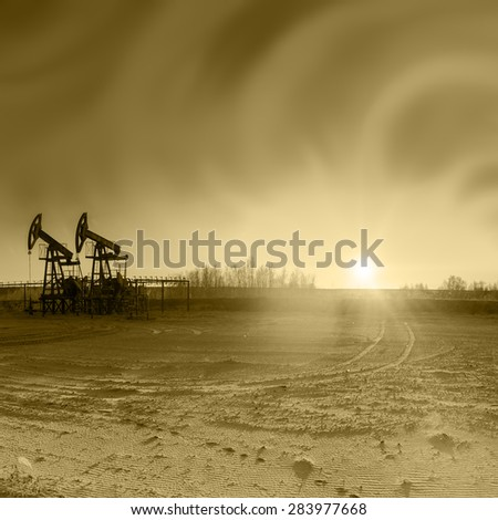 Oil pumps on the sunset sky background. Toned sepia. - stock photo