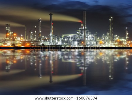 Oil refinery at night with reflection in water - stock photo