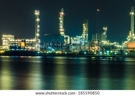 Oil refinery at night with shadow in river, zoom len - stock photo