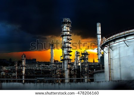Oil refinery at sunset and rain cloud