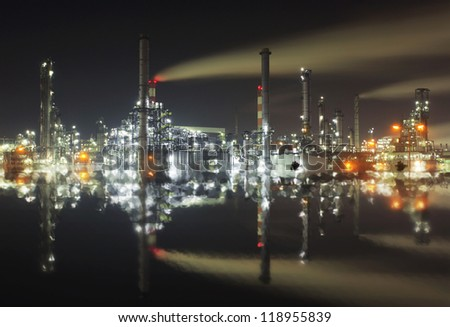 Oil refinery at twilight at night with reflection in water