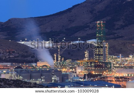 Oil refinery facilities illuminated at night - stock photo