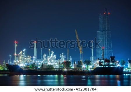 Oil Refinery Industry at night Construction more A cargo ship moored on the river front.