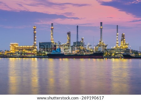 Oil refinery industry plant during twilight morning along with water reflection