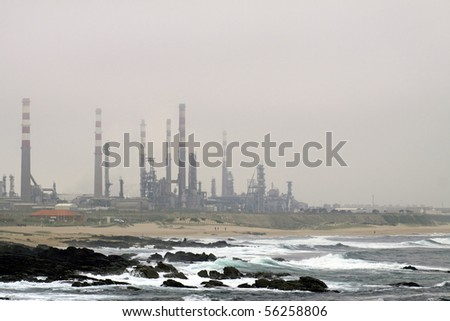 Oil refinery near the sea in a misty late evening - stock photo