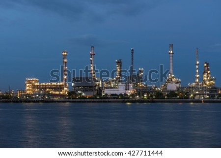 Oil refinery near water with blue sky at twilight