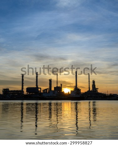Oil refinery or petrochemical industry plant at sunrise in silhouette view with reflection