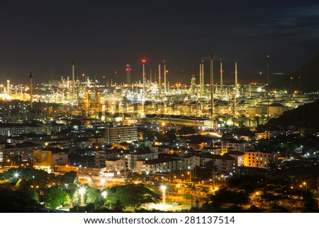 Oil refinery plant area at middle city in night - stock photo