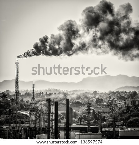 Oil refinery polluting the air with a huge smoke column - stock photo