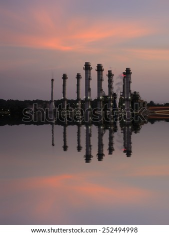 Oil Refinery reflected light water sunset industry in thailand and twilight tone. - stock photo