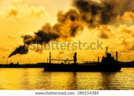 Oil refinery releasing a huge smoke column polluting the air with the silhouette of a ship on the foreground - stock photo