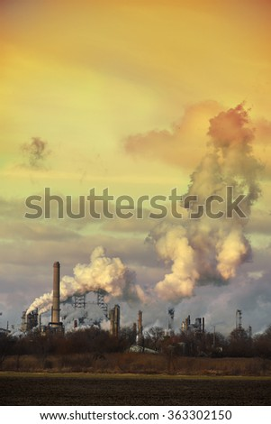 Oil refinery spewing gases from smoke stacks at sunset - stock photo